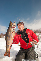 Angler holding a winter brook trout caught ice fishing.