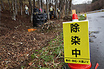 A sign warning people about decontamination chemicals being used where workmen are removing undergrowth and topsoil along a road near Katsurao in rural Fukushima, Japan, Wednesday May 1st 2013.  The Japanese government has decided to remove the topsoil and vegetation from the areas affected by radiation after the disaster at Fukushima Daichi nuclear plant on March 11th 2011