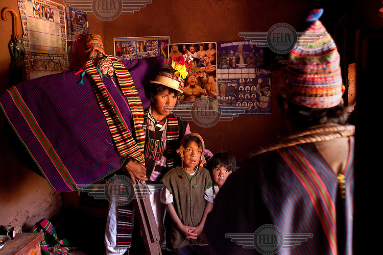 Teofilo Torres holds the Santa Cruz or Holy Cross, in his house in a ceremony in the tiny community of Villa Ventilla, near Macha. <br /> <br /> The people of Macha and surrounding communities carry on the pre-Columbian tradition of ritual fighting. The communities gather on the plaza of Macha to fight and dance in competition with each other. The blood that is spilled is an offering to Mother Earth. In return, the people ask for rain and a good harvest. This ritual is called tinku or fiesta de la cruz since the cross is also engaged in the festivities. The cross is dressed up, given offerings and brought from communities around Macha to the church in town. This syncretic festival melds pagan, pre-christian rituals with Catholic practice. /Felix Features