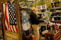 Shopper Eddie Broussard, Hickory, North Carolina looks at an early 1900 Jesus  litho. The litho is just one of the thousands of unique items available for purchase at the Depot at Gibson Mill.The Depot at Gibson Mill, an antique and designer mall that was once a mill, located in Concord, N.C. With 85,000 square feet and 460 booths, we have quickly become the largest antique and designer mall in the South. Once a part of the old Cannon Mills, the charm of the 20 foot ceilings, wide wooden floors and exposed brick remains. Photo is part of a photographic series of images featuring Concord, NC, by Charlotte-based photographer Patrick Schneider..