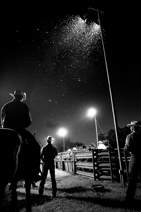 Thirst for Grit - Rodeo Bull Riders.  Spectators and participants watch under the arena lights at the Mason, Texas rodeo on July 14, 2007.