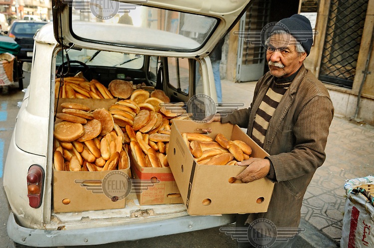 A man delivering bread from the back of a battered old Renault car.