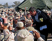 Robin Williams shakes hands and poses for photos with some of the troops gathered at the Camp Liberty Post Exchange in Baghdad, Iraq, during a United Services Organization tour on December 14, 2004. Williams joined Chairman of the Joint Chiefs of Staff General Richard B. Myers, United States Air Force, Blake Clarke, John Elway and Leann Tweedon on the USO tour to meet, entertain and thank the deployed troops..Mandatory Credit: Dan Purcell / U.S. Army via CNP
