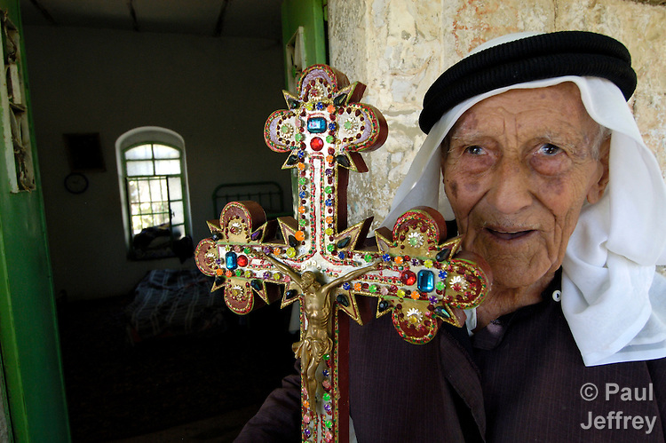 A Palestinian man, a member of the Greek Orthodox church in the small West Bank village of Aboud, holds a cross he carved himself. Christians are a diminishing minority in the Holy Land; many have emigrated abroad to escape violence and the economic hardships imposed upon Palestinians by the Israeli occupation.