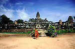 A young novice monk runs past a temple in the complex at Angkor, Cambodia