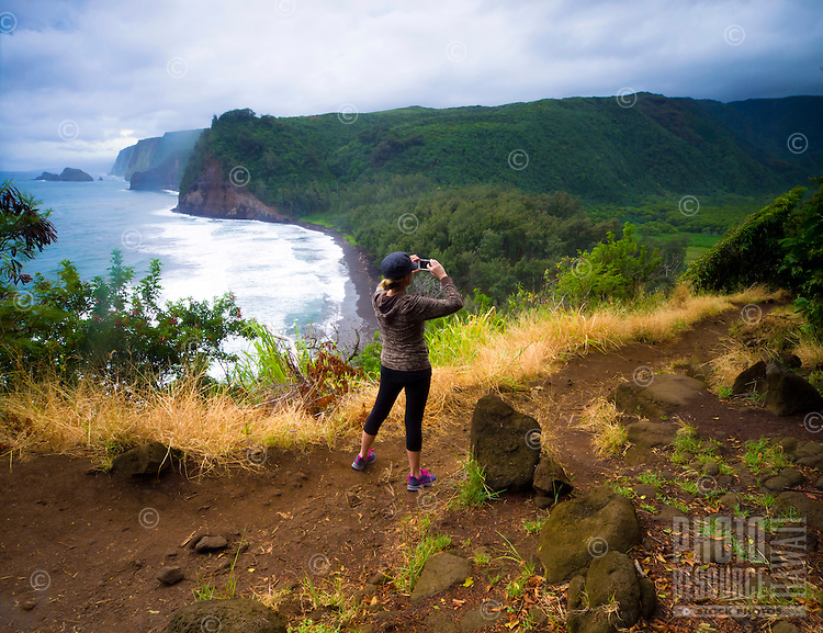 A female tourist takes a picture of Pololu Valley with her smart phone from a hiking trail, Hawi, Island of Hawai'i.