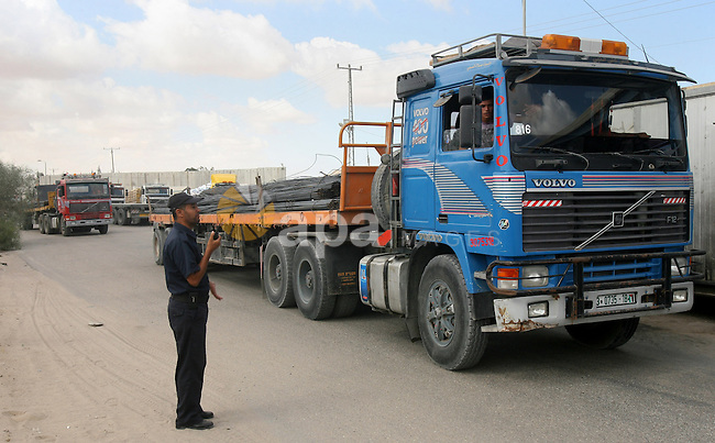 A Palestinian policeman stands near trucks loaded with cement supplies after upon arrival to the town of Rafah through the Kerem Shalom crossing between Israel and the southern Gaza September 22, 2013. Israel began allowing construction material for private projects into the Gaza Strip on Sunday for the first time in six years, in response to a request from Palestinian President Mahmoud Abbas, an Israeli defence official said. Photo by Eyad Al Baba