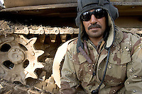 Iraqi tank commander Addil Amir from the 1st company, 1st armour battalion of the 1st mechanized Iraqi Army Brigade seeks cover in back of his tank  while conducting  patrols, check points and observation posts on code name route Michigan, the main road of Ramadi in the week during the national election on WED Dec 14 2005 in Ramadi, Iraq. 1st company is part of the first armor battalion of the New Iraqi Army. it has started its training in January 2005. after 50 days their 35 russian and chinese built T 55 tanks begun conducting operations under the guidance of a US military adivisor team. in April 2005 they patrolled in the Abu Ghraib area concluding their first significant mission. While these old tanks are rolling on the ramadi streets more modern T72s are getting ready to become fully operational in Taji, their main base. the Iraqi army wanted to show their power in ramadi during the Dec 15 elections displaying their new armour company. but like all the other Iraqi forces they are not going to secure the polling sites, staying in the rear with the rest of the iraqi and coalition forces. T 55s are very old tanks. production begun in the late 50s to the late 70s. athough obsolete many countries still use the T55 as their main heavy armoured combat vehicle. slow, heavvy and with very little room for the crew it suffers from many mechanical problems constantly challenging the iraqi mechanics and engineers.