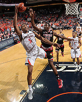 Virginia forward Darion Atkins (5) shoots next to Louisville forward/center Chinanu Onuaku (32) during the second half of an NCAA basketball game Saturday Feb. 7, 2015, in Charlottesville, Va. Virginia defeated Louisville  52-47. (Photo/Andrew Shurtleff)