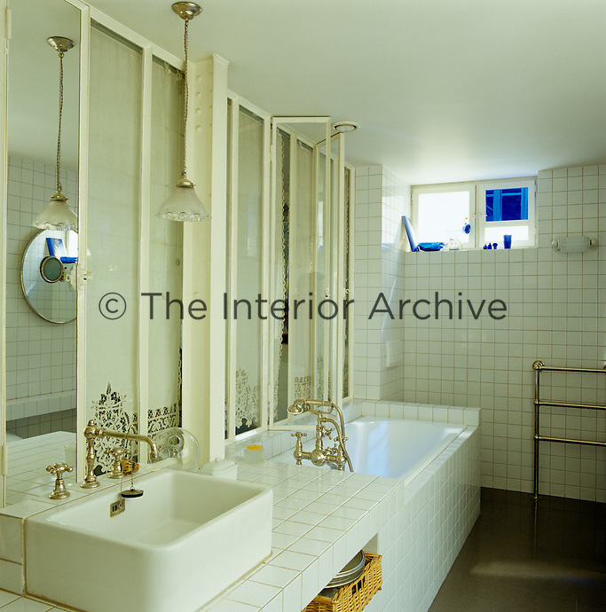 The bathroom has a distincly fin-de-siecle feel due to a triple set of long glass windows faced with embroidered white curtains and is entirely clad in pearly ceramic tiles