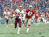 Washington, D.C. - January 8, 1984 -- Washington Redskins wide receiver Charlie Brown (87) runs with the ball after catching a pass from quarterback Joe Theismann (7) late in the third quarter in the NFC Championship game at RFK Stadium in Washington, D.C.  He is being pursued by San Francisco 49ers left cornerback Ronnie Lott (42).  Brown scored the Redskins third touchdown on the 70 yard play.   Tight end Don Warren (85) follows on the play.  The Redskins won the game 24 - 21 to go to Super Bowl XVIII.<br /> Credit: Howard L.  Sachs / CNP