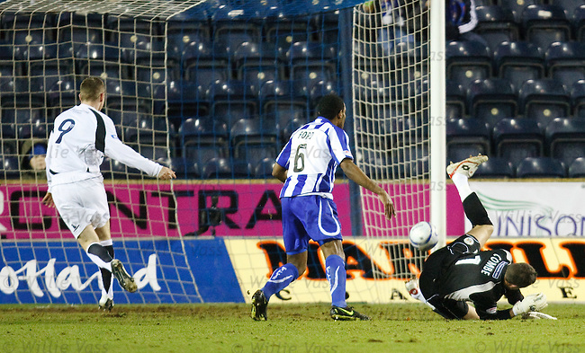 Bryan Prunty punches the ball into the net as Simon Ford and Alan Combe mix it all up.