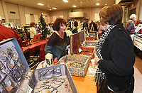 NWA Democrat-Gazette/FLIP PUTTHOFF<br /> LOOKING A LOT LIKE CHRISTMAS<br /> Jackie Charles (left) helps customers select jewelry at her table on Saturday Nov. 11 2017 at the Bella Vista Christmas Bazaar. Dozens of vendors sold holiday items and served refreshments at the event held at Riordan Hall in Bella Vista.
