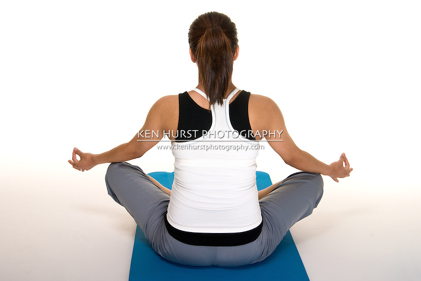 Beautiful young, Hispanic woman meditating in a yoga fitness workout to keep herself physically fit during her pregnancy.  Model has her back toward the camera. Shot on white background.