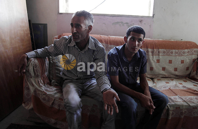 Ahmed Obaid (R), 18, a mentally disabled Palestinian youth, sits with his father at their home in Issawiya neighborhood in Jerusalem on 02 September 2013. Israeli security forces arrested Obaid during a protest against killing of three Palestinians in Qalandiya refugee camp. He was released on bail on Monday after spending a week in jail under torture. Photo by Saeed Qaq