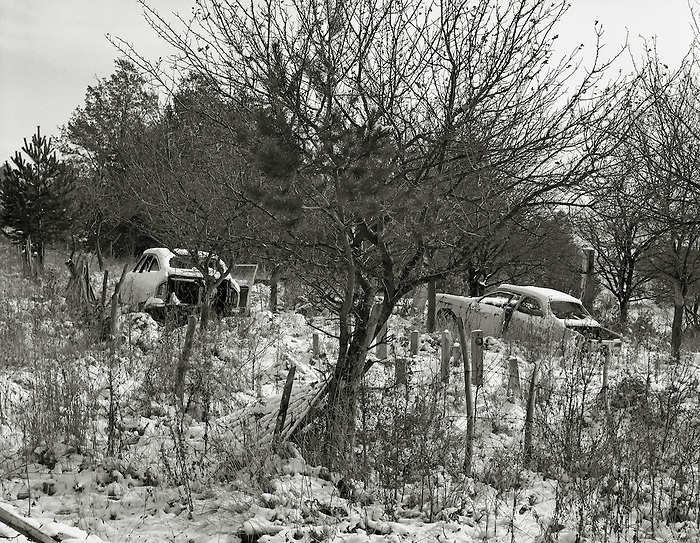 Snow covered car wrecks by the road in North-West Bosnia. 1997.