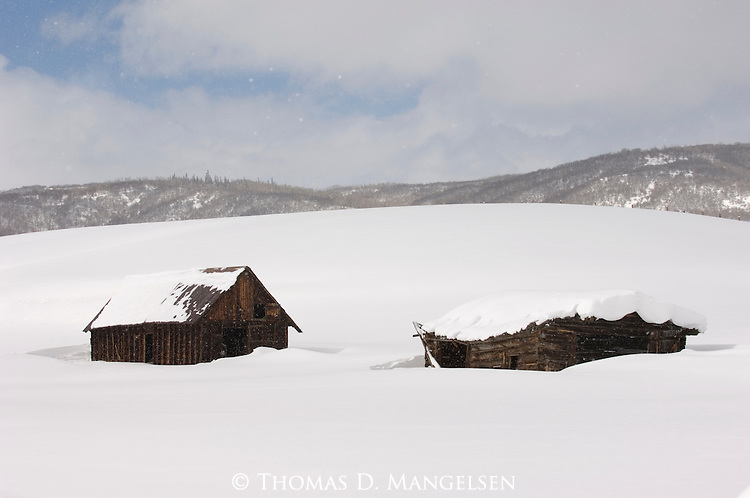 Two old buildings in a snow covered field in Colorado.