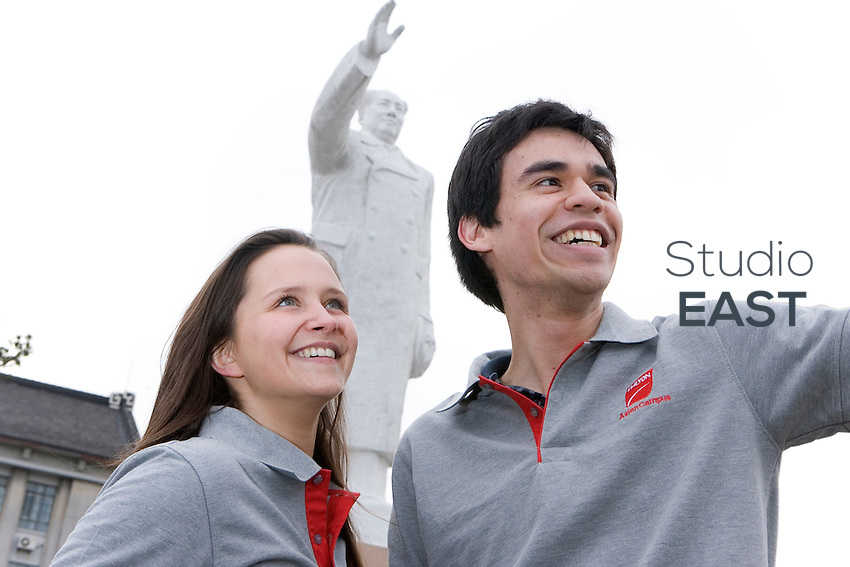 EMLyon Business School students Marie Allilaire, left, and Patrick Baraut, right, pose by a statue of Mao Zedong, in the attitude of communist pioneers, in Shanghai, China, on April 7, 2010. Photo by Lucas Schifres/Pictobank