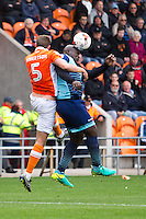 Adebayo Akinfenwa of Wycombe Wanderers heads the ball under pressure from Clark Robertson of Blackpool during the Sky Bet League 2 match between Blackpool and Wycombe Wanderers at Bloomfield Road, Blackpool, England on 20 August 2016. Photo by James Williamson / PRiME Media Images.