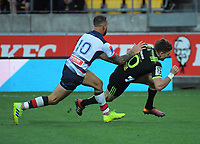 Quade Cooper tries to tackle Beauden Barrett during the Super Rugby match between the Hurricanes and Rebels at Westpac Stadium in Wellington, New Zealand on Saturday, 4 May 2019. Photo: Dave Lintott / lintottphoto.co.nz
