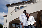SOWETO, SOUTH AFRICA - MAY 15: Event agency owner Palesa Gcaba stands with her husband Sifiso outside their posh house on May 15, 2010, in Soweto, South Africa. Palesa is part of the new young generation of black South African's who has obtained a better education and opportunities than their parents. She organizes big events for government departments and private business. Because of being  black and a women, she can tender for government contracts much easier than being a white person. She grew up in Soweto but lives in a posh Johannesburg suburb and drives a late model BMW. Soweto is the largest township in South Africa, located about 10 kilometers southwest of downtown Johannesburg. The population is estimated to be around 2-3 million. (Photo by Per-Anders Pettersson)