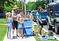 A dimly prepares to hit the beach by applying sun screen after the Independence Parade Saturday July 2, 2016 on Beach Avenue in Cape May, New Jersey. Photo by William Thomas Cain/Cain Images