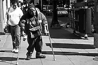 Seen struggling on a downtown Chicago street spring 2011. He carries with him a paper cup for donations from passersby.