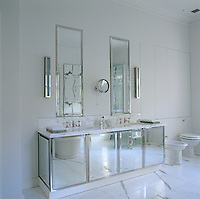 The use of mirrors on the walls and cabinets of this sophisticated bathroom make it appear brighter and larger