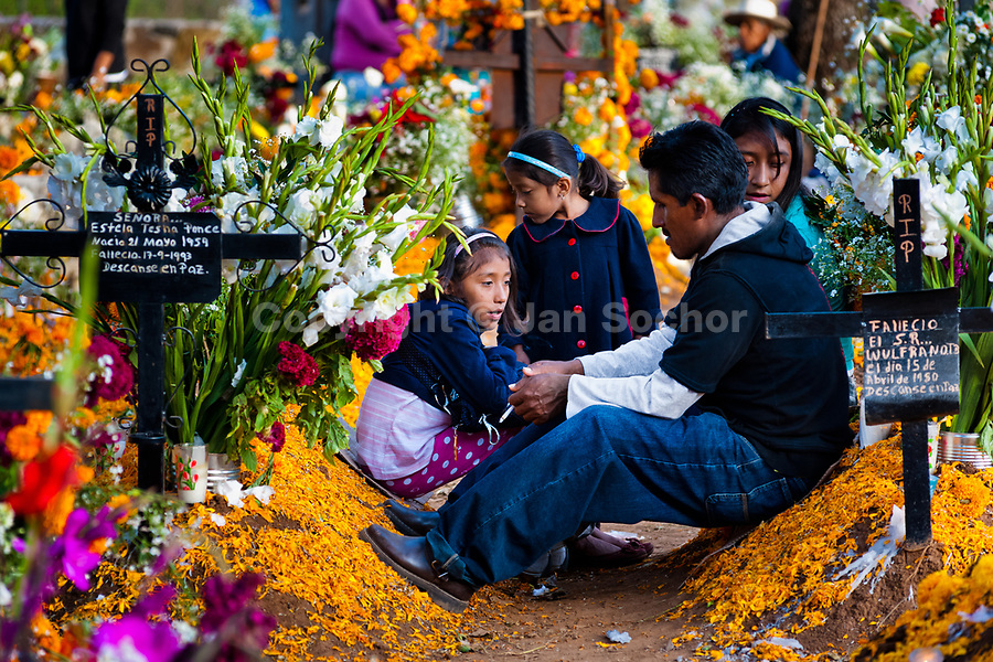 A Mexican family gathers at the flower-decorated grave to honor the deceased relatives during the Day of the Dead festivities in Tzurumútaro, Michoacán, Mexico, 3 November 2014. Day of the Dead ('Día de Muertos') is a syncretic religious holiday, celebrated throughout Mexico, combining the death veneration rituals of the ancient Aztec culture with the Catholic practice. Based on the belief that the souls of the departed may come back to this world on that day, people gather on the gravesites praying, drinking and playing music, to joyfully remember friends or family members who have died and to support their souls on the spiritual journey.