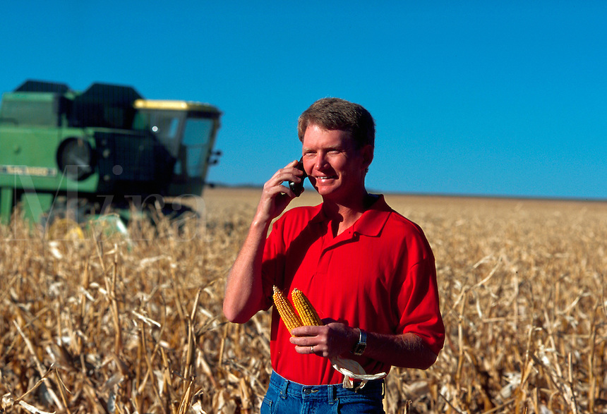Farmer standing in his cornfield talking on a cell phone.