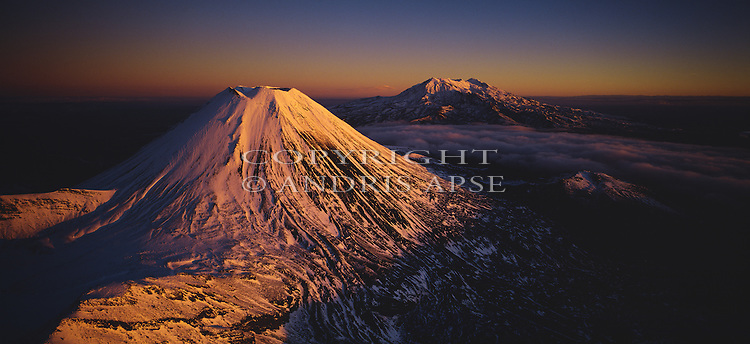 Aerial of snow covered Mount Ngauruhoe at sunrise. Mount Ruapehu in background. Tongariro National Park. New Zealand.