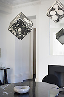 The dining room is furnished with a veined black marble table with photo cubes by Tony Battaglia suspended from the ceiling above
