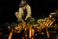 "Salvager Larry McCullough packs up his prize find - 300lbs. of 50mm brass shell casings - on the Marine bombing range next to Slab City in the Chocolate Mountains. McCullough has been salvaging brass and aluminum from bombs and shell casing in the range for the last 25 years. Asked if he felt this was dangerous work, he replied, ""Well they bomb nearly every day, but I feel I know their routine. Besides this is good for them, me cleaning up all of this junk."" He added, ""Whoa, tonight I hit the motherload."" Tonight's find will net him somewhere close to a thousand dollars."