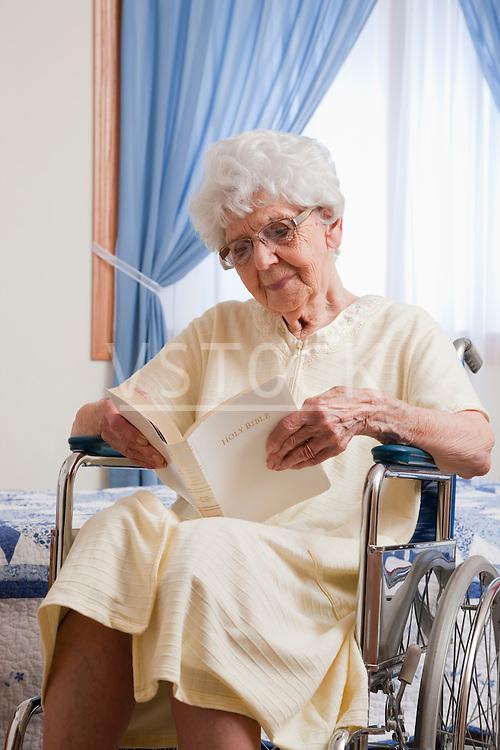 USA, Illinois, Metamora, Senior woman on wheelchair reading Bible
