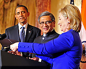 Foreign Minister S.M. Krishna of India, center, smiles as United States Secretary of State Hillary Rodham Clinton, right, helps him with his notes during a reception in the Minister's honor at  at the State Department  in Washington, D.C. on Thursday, June 3, 2010.  U.S. President Barack Obama looks on from the left..Credit: Ron Sachs - Pool via CNP