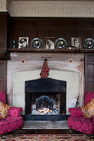 A pair of newly upholstered armchairs in fuschia pink flanks the fireplace in the music room