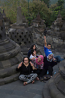 Borobudur, Java, Indonesia.  Indonesian Family Posing for their Picture between two Stupas.  The V is a common gesture in Indonesia when the person being photographed wants the photo to be a good one.