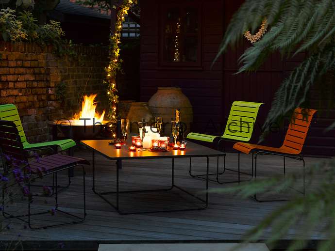 A brazier and fairylights provide background lighting for brightly coloured metal chairs and a candlelit table
