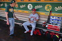 OAKLAND, CA - MARCH 31:  Mike Trout #27 of the Los Angeles Angels of Anaheim talks to Oakland Athletics team photographer Michael Zagaris in the dugout before their game at the Oakland Coliseum on Saturday, March 31, 2018 in Oakland, California. (Photo by Brad Mangin)