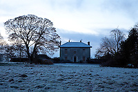 A wintery landscape of frosty tufts of grass and silhouetted trees surrounds Burtown House
