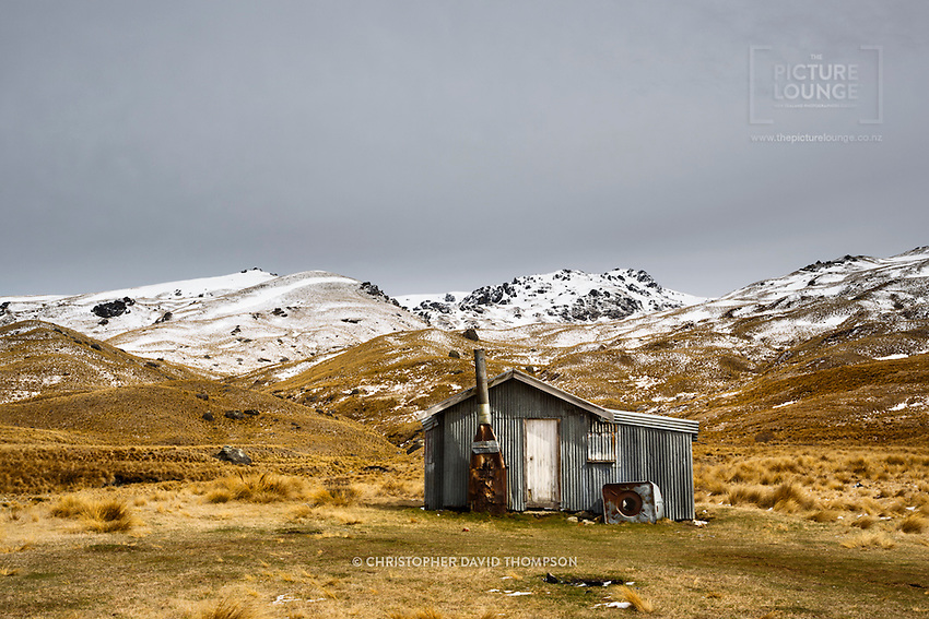 An old musterers hut or crib sits abandoned and neglected amongst the vast landscape of the Nevis Valley, visited here at the best time when the winter's snows are still lingering, photographed by NZ landscape photographer - Christopher David Thompson.