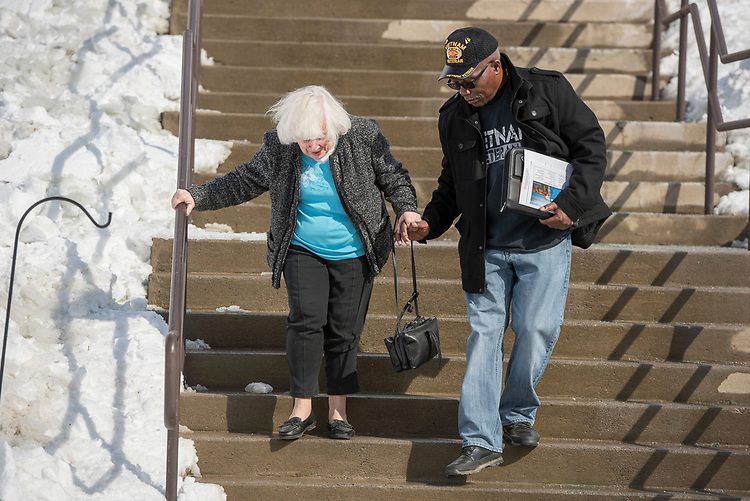 UNITED STATES - MARCH 16: Mossie Wright, 65, helps Nellie Thompson, 80, down steps before a town hall with Sen. Joe Manchin, D-W.Va., at the WVU Robert C. Byrd Health Sciences Center in Martinsburg, W.Va., March 16, 2017. Much of the discussion was regarding the American Health Care Act, the Republican's plan to repeal and replace the ACA. (Photo By Tom Williams/CQ Roll Call)