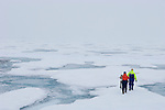 Scientists on an ice floe with a beacon to search for the location of researcher submersibles under the ice, and carrying a shotgun in case of a Polar Bear attack, Arctic Ocean.