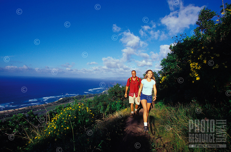 Happy couple enjoying hiking on Kealia Trail, with North Shore ocean in background, Mokuleia,  near Haleiwa, Oahu, Hawaii