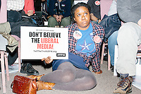 "Ebony Ellise, of Houston, Tex., holds a sign reading ""Don't Believe the Liberal Media,"" as Texas senator and Republican presidential candidate Ted Cruz speaks at a town hall at Crossing Life Church in Windham, New Hampshire, on Tues. Feb. 2, 2016. The day before, Cruz won the Iowa caucus."