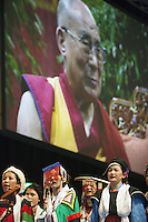 "Switzerland. Basel. St. Jakobshalle. A group of tibetan women dressed in traditional clothings and His Holiness the Dalai Lama. The 14th and current Dalai Lama is Tenzin Gyatso, recognized since 1950. He is the current Dalai Lama, as well as the longest-lived incumbent, well known for his lifelong advocacy for Tibetans inside and outside Tibet. Dalai Lamas are amongst the head monks of the Gelug school, the newest of the schools of Tibetan Buddhism. The Dalai Lama, also called "" Ocean of Wisdom"" is considered as the incarnation of Chenresi, the Bodhisattva of compassion who is also the protective deity of Tibet. The man in front is a tibetan man working as a body and security man for the Dalai Lama. 8.02.2015 © 2015 Didier Ruef"