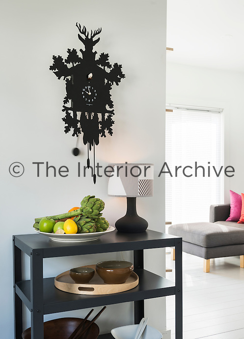 A black cuckoo clock hangs on the wall above a plain side table with a shelf below. A lamp, designed by Eva Whitmore, bowl of fruit and ceramic bowls are displayed on the table.