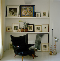 A collection of framed paintings, prints and black and white photographs is displayed on shelves behind this retro black leather armchair