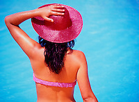 Rear view of sexy woman in a bikini, poolside, wearing a red hat.  Model Released..