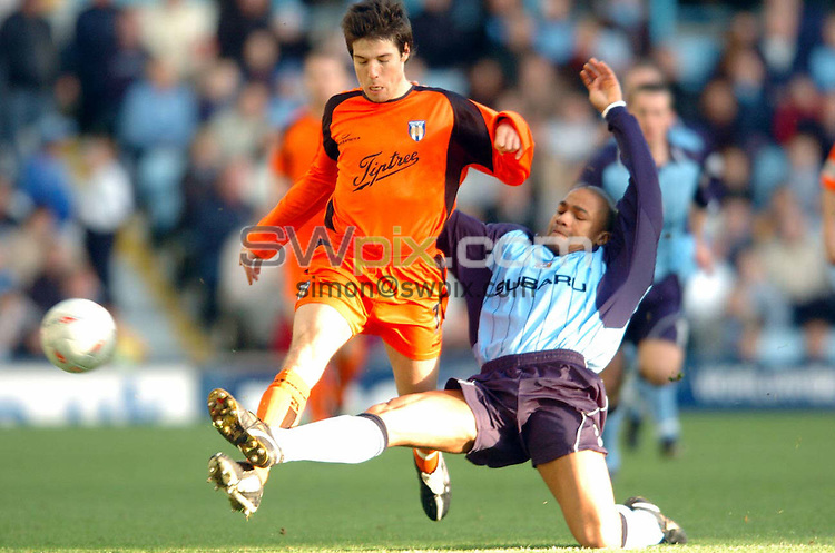 Pix: Matthew Lewis/SWpix.com. Soccer. FA Challenge Cup Fourth Round. Coventry v Colchester. 24/01/04...COPYRIGHT PICTURE>>SIMON WILKINSON>>08700920092>>..Coventry's Eric Deloumeaux tackles Colchester's Kem Izzet.